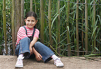 Girl (5-6) sitting in front of fence portrait