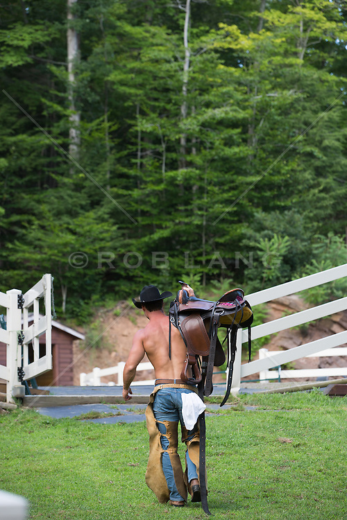 shirtless cowboy in chaps carrying a saddle to the barn