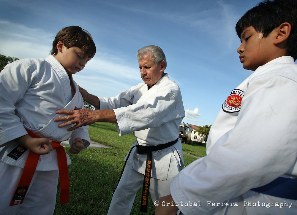Karate coach Vicente Gonzalez, center, teaches Alejandro Casuso, 9,  John Paulo, 10, during their training session at Sunset Lake Community Center on Monday July 6, 2009. Staff photo/Cristobal Herrera..