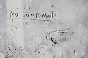 No Junk Mail is scratched into emulsion paint smeared over window of a Healthcare Agency in Brockley Rise,  a victim of the UK recession.