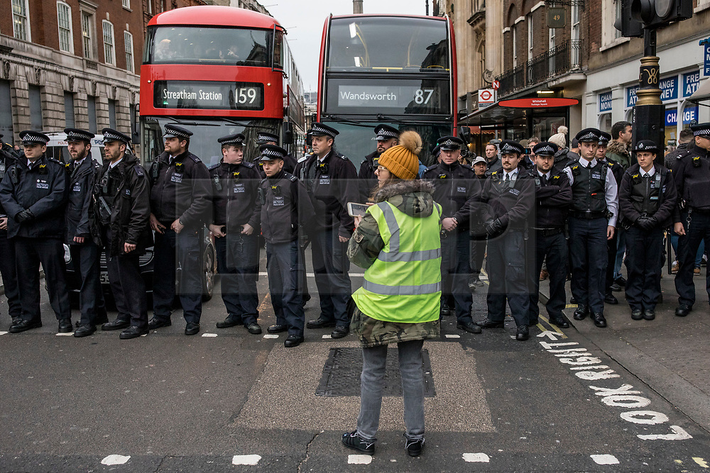 """© Licensed to London News Pictures. 12/01/2019. London, UK. Pro-Brexit """"yellow vest"""" protesters are blocked by police on Whitehall to prevent them from reaching an anti-austerity rally in Trafalgar Square. Photo credit: Rob Pinney/LNP"""