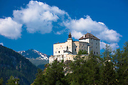 Tarasp Castle surrounded by larch forest in the Lower Engadine Valley, Switzerland
