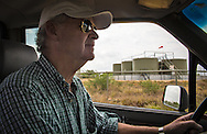 Hugh A. Fitzsimons III, a buffalo rancher  in Carrizo Springs Texas, part of the Eagle Ford Shale,  drives by a fracking industry site near his home.  Fitzsimons concerned with the amount of water the fracking industry uses ran and won a seat on the water-board so he could have a voice in protecting the areas water.