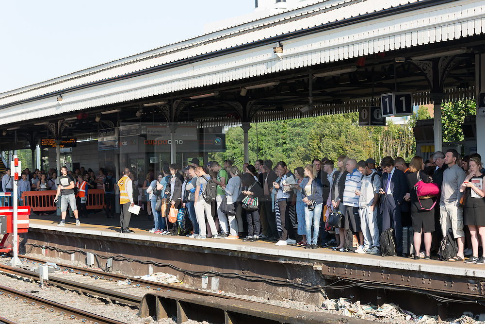 © Licensed to London News Pictures. 09/07/2015. London, UK. Crowded platforms and more passengers wait behind crowd control barriers at Clapham Junction station in south London. A tube strike today has closed the TfL London Underground network and has been called by Trade Unions in protest over the new all-night tube trains, due to start in mid-September.. Photo credit : Vickie Flores/LNP