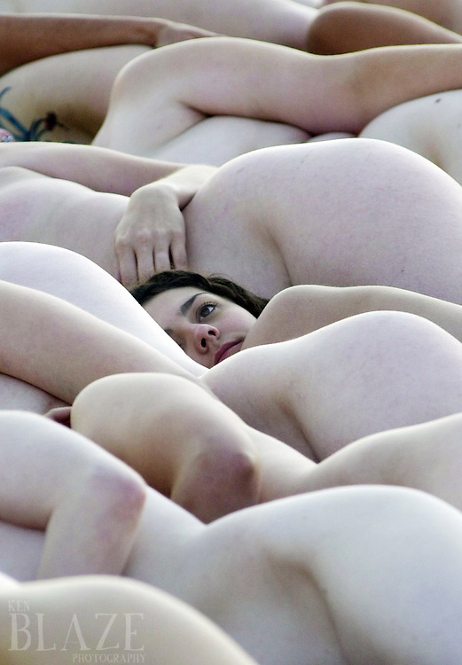 Ken Blaze/News-Herald<br /> A lone face of a woman is a stark contrast to the skin tones in the crowd of all women being photographed by Spencer Tunick Saturday morning at Voinovich Park in Cleveland.