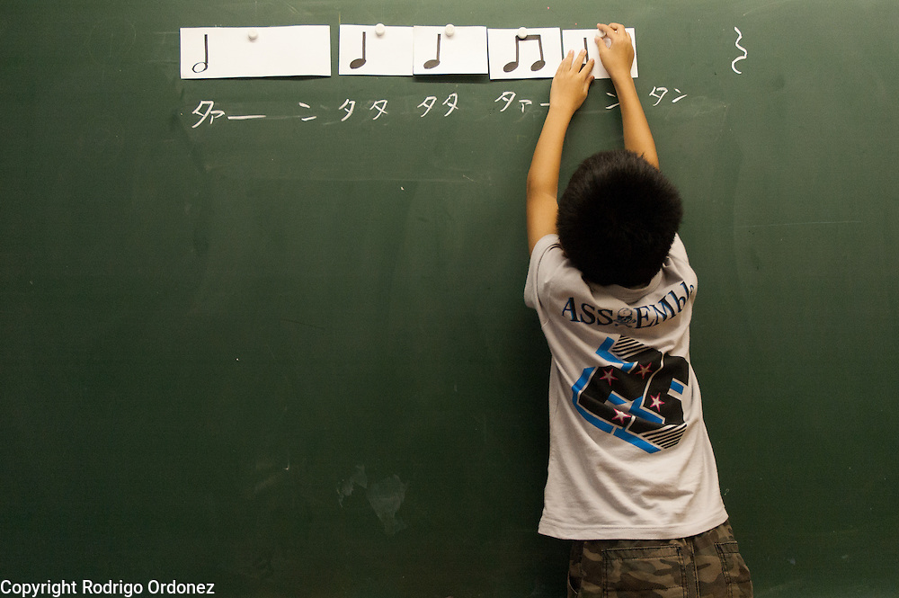 A boy lays musical notes on the blackboard during a music class at Hakusan Primary School in Kamaishi, Japan.