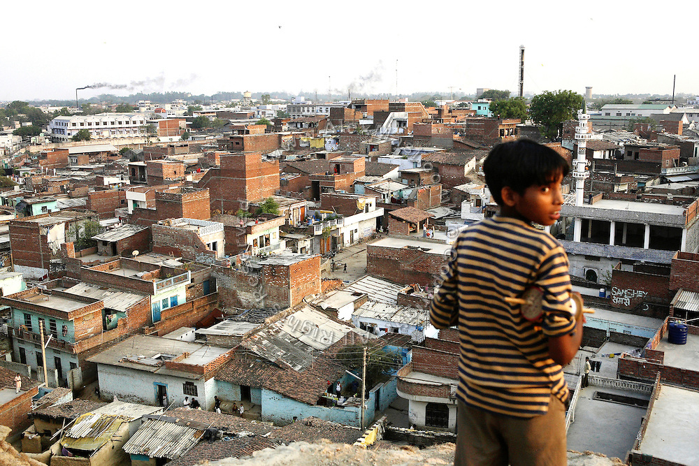 A section of the slum growing along Jajmau Industrial Area in a maze of houses and tannery units is seen from the surrounding hilltop. A local boy is flying his kite, in Kanpur, Uttar Pradesh.