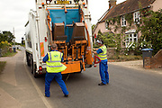 Two men load waste disposal vehicle, Hollesley, Suffolk, England