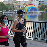 Walkers wearing protective masks due to the Coronavirus (Covid-19) outbreak are seen at Lake Eola Park on Tuesday, April 15, 2020 in Orlando, Florida. (Alex Menendez via AP)