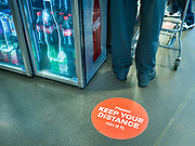 """02 APRIL 2020 - DES MOINES, IOWA: Stickers reminding people to """"Social Distance"""" on the floor of a grocery store in downtown Des Moines. On Saturday morning, 04 April, Iowa reported 786 confirmed cases of the Novel Coronavirus (SARS-CoV-2) and COVID-19. There have been 14 deaths attributed to COVID-19 in Iowa. Restaurants, bars, movie theaters, places that draw crowds are closed until 30 April. The Governor has not ordered """"shelter in place"""" but several Mayors, including the Mayor of Des Moines, have asked residents to stay in their homes for all but the essential needs. People are being encouraged to practice """"social distancing"""" and many businesses are requiring or encouraging employees to telecommute.        PHOTO BY JACK KURTZ"""