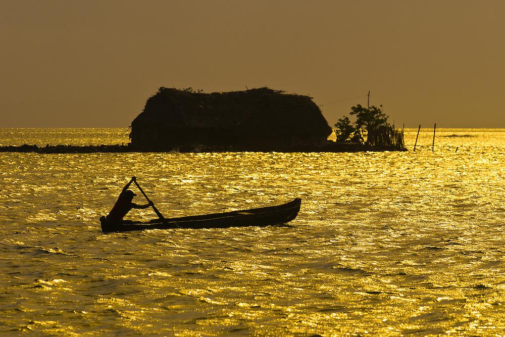 Kuna Indian rowing dugout canoe in front of a hut on small island at sunset, San Blas Islands (Kuna Yala), Caribbean Sea, Panama