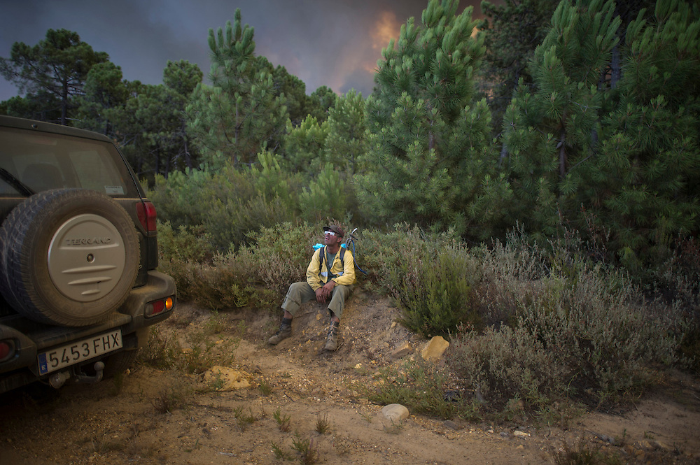 A man rests in wildfire in Tabuyo del Monte near Leon on August 20, 2012. Numerous wildfires have broken out across Spain in the sweltering heat in recent weeks, an extra headache for authorities struggling to get the country out of its financial crisis and recession. © Pedro ARMESTRE
