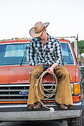 cowboy sitting on top of an old pickup truck outdoors