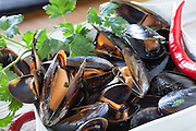 Closeup of bowl with mussels saute decorated with fresh parsley and red chili pepper.