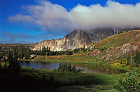 Bellamy Lake below the cloud covered Snowy Range.  Wyoming, USA.