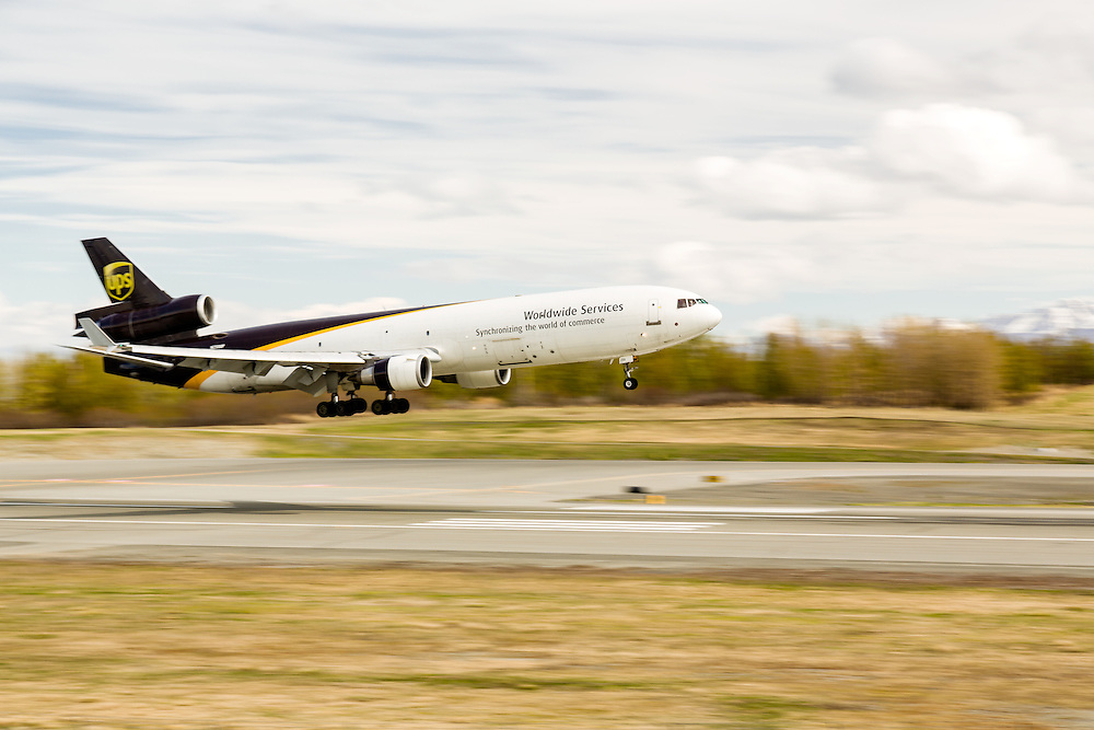 UPS cargo jet landing at Ted Stevens Anchorage International Airport in Southcentral Alaska with the Chugach Mountains in the background. Spring. Afternoon.
