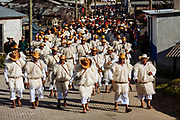 """Al frente policías tradicionales con """"chuj"""" blanco, sombrero, báculo en la espalda y soga dentro del """"chuj"""".<br /> Les siguen los escribanos con """"chuj"""" blanco, sombrero y cinturón de cuero. Atrás el H. Consejo Municipal, que portan """"chuj"""" negro, sombrero con listones y bastón de mando. Juntos se dirigen al cabildo, después de participar en los ritos en casa del Paxon del barrio de San Juan. desde el balcón presidencial observarán los tres recorridos que los patones y su comitiva darán a la plaza."""