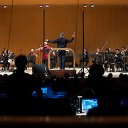 """June 8, 2012 - New York, NY : David Robertson, standing at center, conducts the New York Philharmonic in Pierre Boulez's """"...explosante-fixe..."""" (1991-93), with computer music design, production, and sound engineering by IRCAM, during The Metropolitan Museum of Art's Presentation of """"CONTACT!,"""" the new-music series of the New York Philharmonic, on Friday night. The piece featured Robert Langevin on MIDI-flute (wearing red). CREDIT: Karsten Moran for The New York Times"""