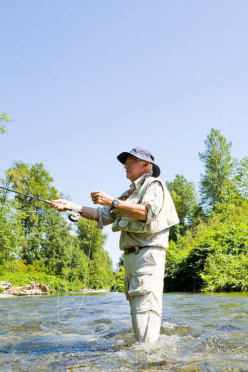 A 70 year old man fly fishing in the Cedar River, Western Washington, USA.