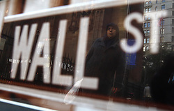 A woman is reflected in a Wall Street sign in New York, New York, USA, 21 October 2008. As Wall Street descend into a financial turmoil not seen since the stock market crash of 1929 and financial businesses were pommeled into rampant sell-offs in stocks and face regulatory changes to their business practices, professionals and non-professionals working in the district's banks, stock-trading houses and insurance companies are showing stress and a gloom not unlike the times of the Great Depression.