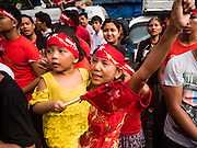 09 NOVEMBER 2015 - YANGON, MYANMAR: A woman and her child at NLD headquarters Monday. Thousands of National League for Democracy (NLD) supporters gathered at NLD headquarters on Shwegondaing Road in central Yangon to celebrate their apparent landslide victory in Myanmar's national elections that took place Sunday. The announcement of official results was delayed repeatedly Monday, but early reports are that the NLD did very well against the incumbent USDP.     PHOTO BY JACK KURTZ