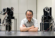 Professor Masatoshi Ishikawa poses with TWO HIGH SPEED VISION CAMERAS developed at Ishikawa-Oku lab at the University of Tokyo, Tokyo, Japan. Photographer: Robert Gilhooly