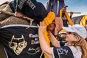 """28 AUGUST 2014 - BANGKOK, THAILAND:     A polo player hands her mahout a marigold flower garland before the King's Cup Elephant Polo Tournament at VR Sports Club in Samut Prakan on the outskirts of Bangkok, Thailand. Each elephant carries two people, the polo player and mahout, who actually controls the elephant. The tournament's primary sponsor in Anantara Resorts. This is the 13th year for the King's Cup Elephant Polo Tournament. The sport of elephant polo started in Nepal in 1982. Proceeds from the King's Cup tournament goes to help rehabilitate elephants rescued from abuse. Each team has three players and three elephants. Matches take place on a pitch (field) 80 meters by 48 meters using standard polo balls. The game is divided into two 7 minute """"chukkas"""" or halves.  PHOTO BY JACK KURTZ"""