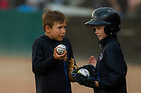 KELOWNA, CANADA - JUNE 28: Young bat boys gets autographs in the dugout during the opening charity game of the Home Base Slo-Pitch Tournament fundraiser for the Kelowna General Hospital Foundation JoeAnna's House on June 28, 2019 at Elk's Stadium in Kelowna, British Columbia, Canada.  (Photo by Marissa Baecker/Shoot the Breeze)