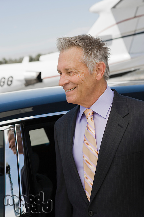 Senior businessman in front of limousine and private jet.