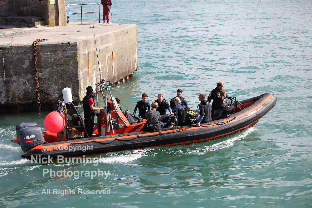 """Newquay Harbour, Newquay, Cornwall, August 6, 2015.  High tide and a sunny morning brings a range of tourist activities to Newquay Harbour. The """"Tornado"""" boat heads out with diving passengers."""