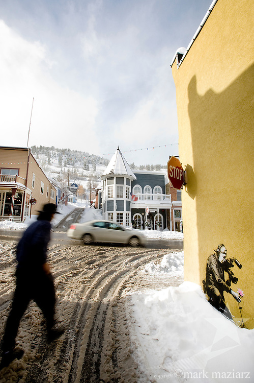 UK street artist Banksy tagged the side of a coffee & ice cream shop on Main Street in Park City, Utah during Sundance Film Festival January 2010.  The art features a camera man pulling a flower from the ground, exposing its roots.