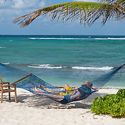 Couple enjoying vacation time on hammock. Wyndham Reef Resort. East End. Grand Cayman Island.