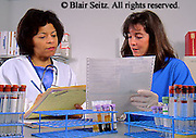 Medical Lab Technicians Consult with Test Result Printouts