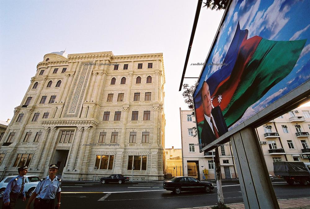 """Der verstorbene autokratische Präsident Heydar Alijew ist überall in der aserbaidschanischen Hauptstadt Baku auf Plakatwänden zu sehen. Auch vor dem Gebäude der staatlichen Ölgesellschaft (hinten) blickt er auf die Menschen herab, während Polizisten überwachen, dass niemand Fotos von dem Gebäude macht, da Einrichtungen der Ölindustrie """"strategische Bedeutung"""" in dem Land am Kaspischen Meer haben. A billboard in front of oil industry related office building shows former aserbaijani president Heyder Aliev."""