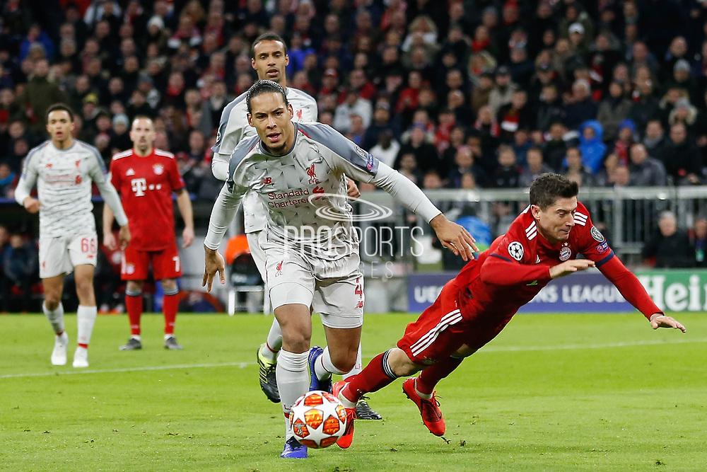 Bayern Munich forward Robert Lewandowski (9) dives as Liverpool defender Virgil van Dijk (4) controls the ball during the Champions League match between Bayern Munich and Liverpool at the Allianz Arena, Munich, Germany, on 13 March 2019.