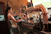 Interior of an Irish style pub draught beer taps. Barmaid pouring a glass of Murphy's Stout
