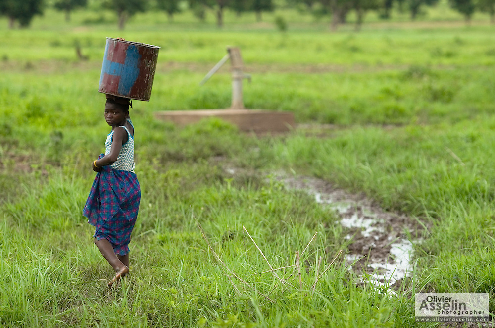 A girl looks back as she approaches a borehole where she'll fill her bucket with water near the village of Ying, Ghana on Monday June 4, 2007.