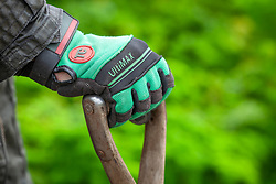 Gloved hand holding a spade
