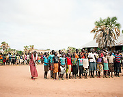 "NUBA MOUNTAINS, SUDAN – JUNE 9, 2018: Schoolteacher Medina Tutu Kafe instructs her choir students at Kororak School. <br /> <br /> In 2011, the government of Sudan expelled all humanitarian groups from the country's Nuba Mountains. Since then, the Antonov aircraft has terrorized the Nuba people, dropping more than 4,080 bombs on hospitals, schools, marketplaces and churches. Today, vestiges of the Antonov riddle the landscapes of daily life, where more than 1 million Nuba live in famine conditions – quietly enduring the humanitarian blockade intended to drive them out of the region. The skies are mostly clear. Yet the collective memory of the bombings remains an open wound, and the Antonov itself a persistent threat. So frequent were the attacks that the Nuba nicknamed the high flying aircraft and its dismal hum: ""Gafal-nia ja,"" they would declare, running to the hillsides. ""The loss of appetite has come."""