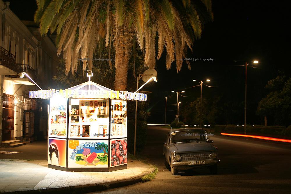 Georgien/Abchasien, Suchumi, 2006-09-02, Ein Eisstand in der nächtlichen Innenstadt von Suchumi. Abchasien erklärte sich 1992 unabhängig von Georgien. Nach einem einjährigen blutigen Krieg zwischen den Abchasen und Georgiern besteht seit 1994 ein brüchiger Waffenstillstand, der von einer UNO-Beobachtermission unter personeller Beteiligung Deutschlands überwacht wird. Trotzdem gibt es, vor allem im Kodorital immer wieder bewaffnete Auseinandersetzungen zwischen den Armee der Länder sowie irregulären Kämpfern. (A little ice cream shop at night in Sokhumi. Abkhazia declared itself independent from Georgia in 1992. After a bloody civil war a UNO mission observing the ceasefire line between Georgia and Abkhazia since 1994. Nevertheless nearly every day armed incidents take place in the Kodori gorge between the both armys and unregular fighters )