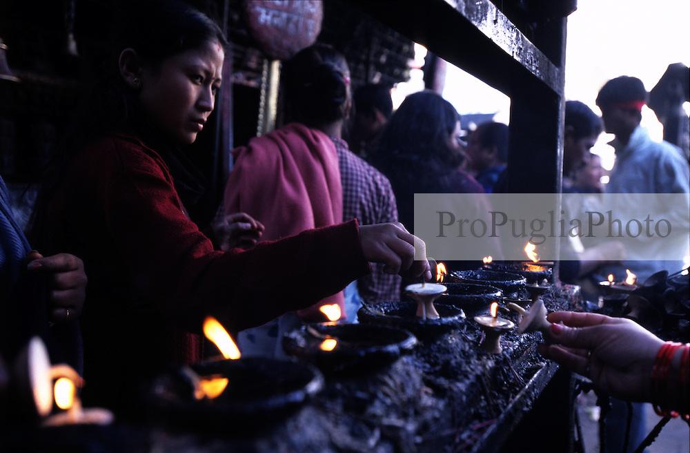 Kathmandu, 13 February 2005. A women lights up a candle to pay respect to Buddha at Swayambhunath Temple
