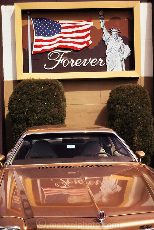 Car dealership sign with the American flag, Statue of Liberty and the word Forever, in Miami, Florida, USA.