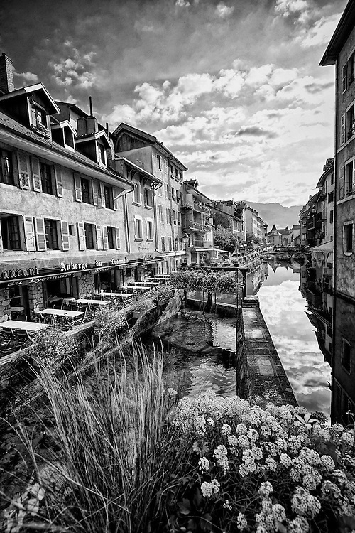 Black and white view of the Auberge du Lyonnais Hôtel/Restaurant and other buildings along the incredible reflective waters of the Thiou Canal, Old Town Annecy, France (Vertical).