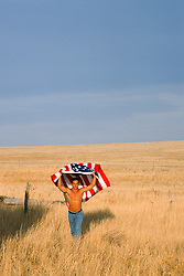 sexy man without a shirt holding an American Flag over his head in a field