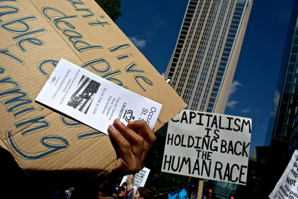 Protestors carry signs while marching through uptown Charlotte two days before the 2012 Democratic National Convention in Charlotte, N.C. on Sept. 2, 2012.