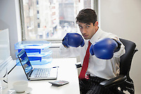 Young Indian businessman wearing boxing gloves at office desk