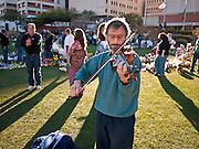 "15 JANUARY 2011 - TUCSON, AZ: MICHAEL SIGLER, from Tucson, plays violin at the memorial on the lawn in front of the University Medical Center in Tucson, AZ, Saturday, January 15. He was playing improvisationally. The memorial has been growing since the mass shooting last week. Six people were killed and 14 injured in the shooting spree at a ""Congress on Your Corner"" event hosted by Congresswoman Gabrielle Giffords at a Safeway grocery store in north Tucson on January 8. Congresswoman Giffords, the intended target of the attack, was shot in the head and seriously injured in the attack. She is hospitalized at UMC. The alleged gunman, Jared Lee Loughner, was wrestled to the ground by bystanders when he stopped shooting to reload the Glock 19 semi-automatic pistol. Loughner is currently in federal custody at a medium security prison near Phoenix.  PHOTO BY JACK KURTZ"