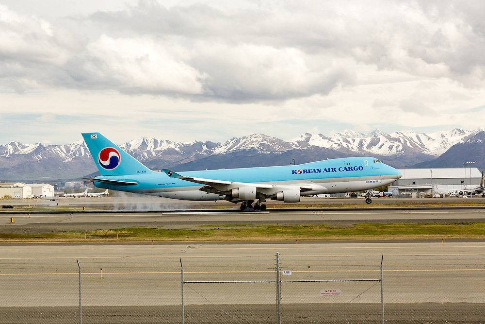 Korean Air Cargo jet landing at Ted Stevens Anchorage International Airport in Southcentral Alaska with the Chugach Mountains in the background. Spring. Afternoon.