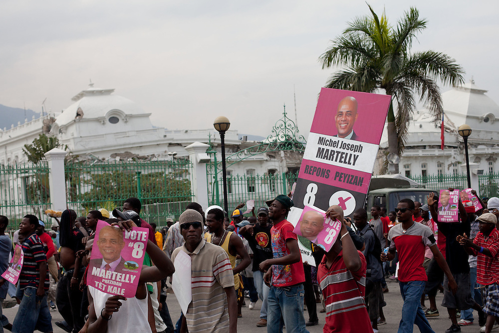 Protesters, many of whom are supporters of Michel Martelly, walk pas the collapsed National Palace. Protestors take to the streets to protest the results of the January 28th election, which were announced last night.