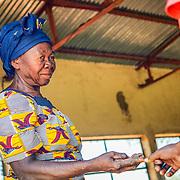 LÉGENDE: La femme perçoit l'argent d'un client pour moudre les noix de Karité. LIEU: Centre COFEMAK, Koumra, Tchad. PERSONNE(S): Femme (à gauche) et client (à droite).